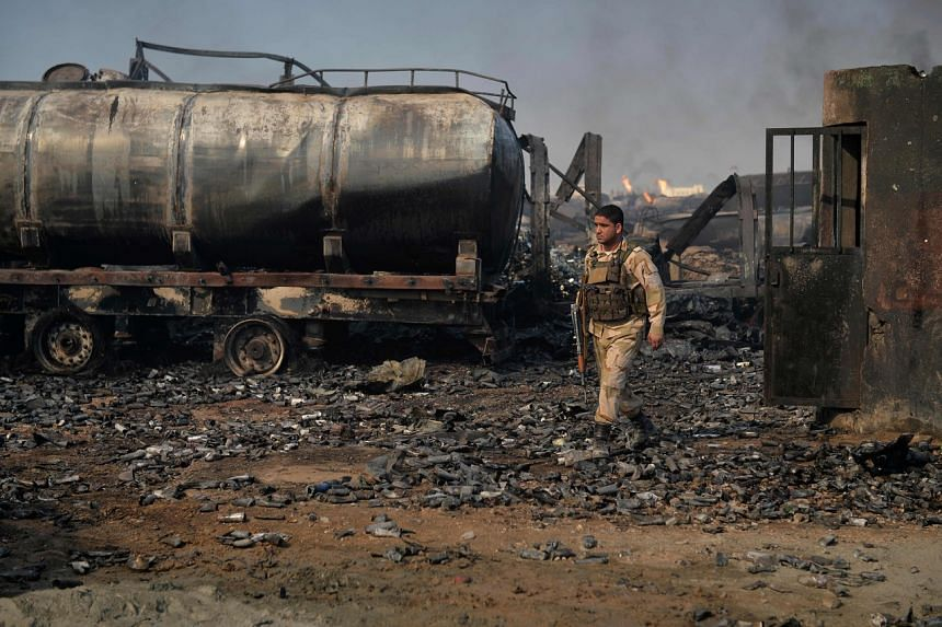 A security forces personnel walks amidst the wreckage of gas tankers at Islam Qala port on Feb 14, 2021.