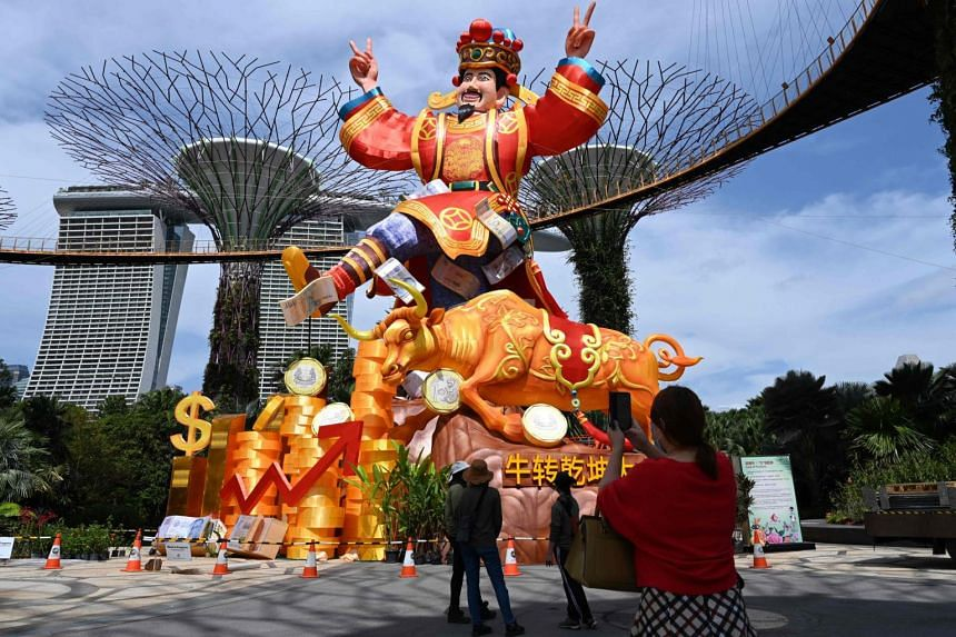"""A woman takes a picture of the """"God of Fortune"""" display at River Hongbao 2021 held at Gardens by the Bay, on Feb 4, 2021."""