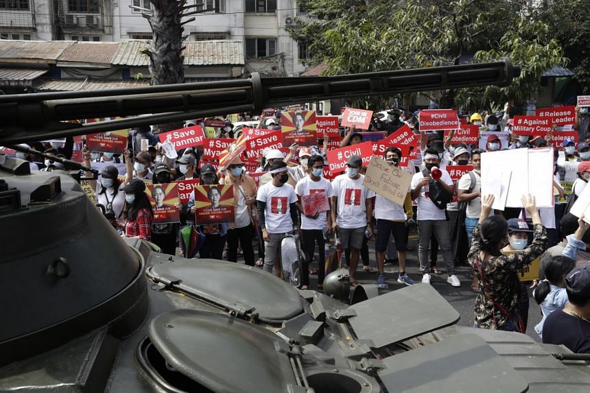 Demonstrators gather near a road where soldiers and armored vehicles are deployed during a protest outside the Central Bank of Myanmar in Yangon, on Feb 15, 2021.