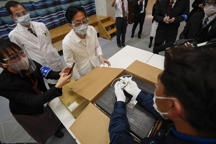 Hospital staff check the condition of Pfizer-BioNTech's Covid-19 vaccines at a Tokyo hospital on Feb 16, 2021.