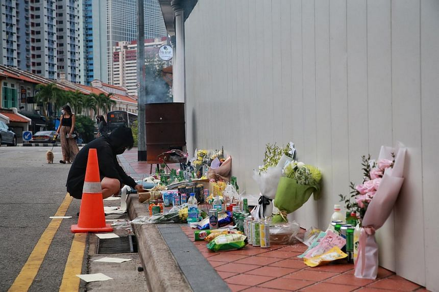 A passer-by places offerings at the site along Tanjong Pagar Road, where five men died after the BMW M4 Coupe they were driving crashed into a shophouse and burst into flames, on Feb 15, 2021.