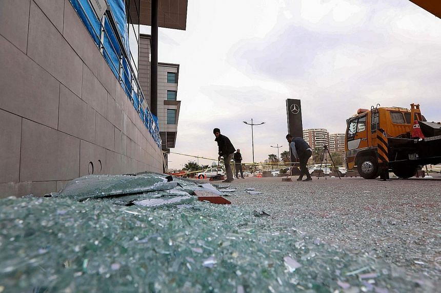 Workers sweeping up shattered glass yesterday outside a damaged shop following Monday's rocket attack in Erbil, the capital of Iraq's Kurdish autonomous region. The attack, claimed by a little-known group that some Iraqi officials say has links to Ir
