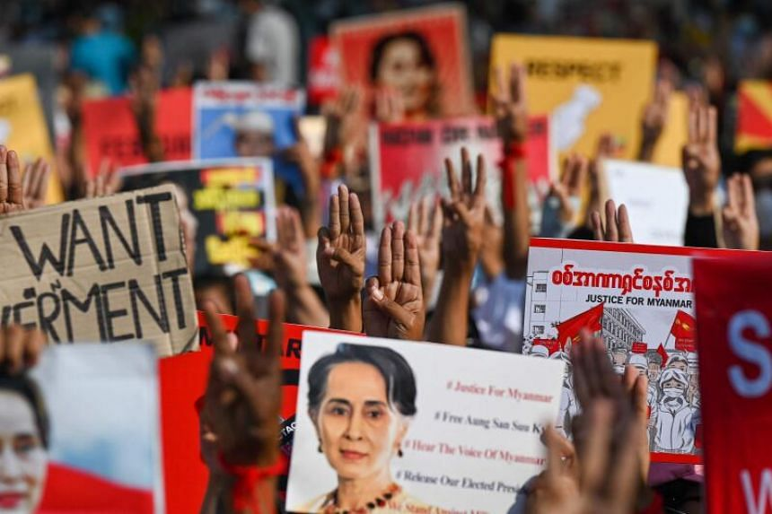 Protesters holding up the three finger salute with signs calling for the release of detained Myanmar civilian leader Aung San Suu Kyi during a demonstration against the military coup in Yangon on Feb 16, 2021.