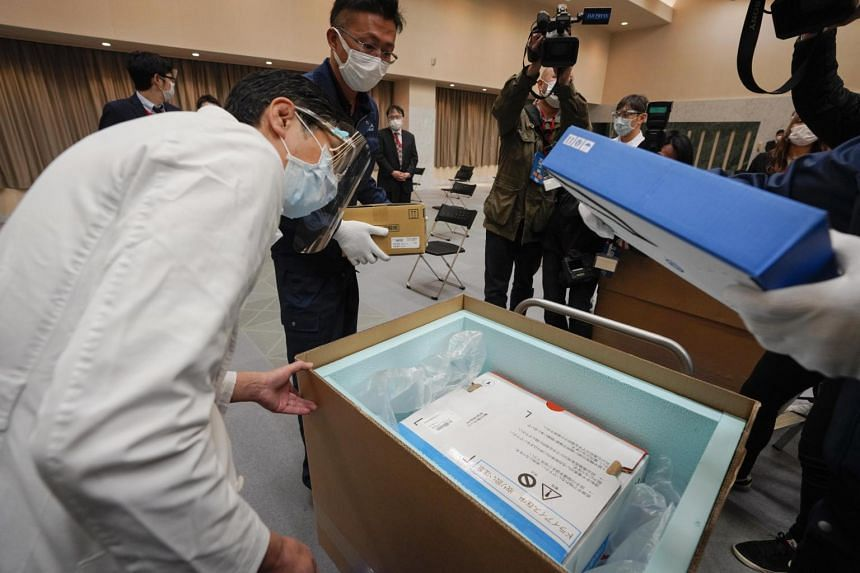Hospital staffs check the condition of Pfizer-BioNTech's Covid-19 vaccines at a Tokyo hospital, on Feb 16, 2021.