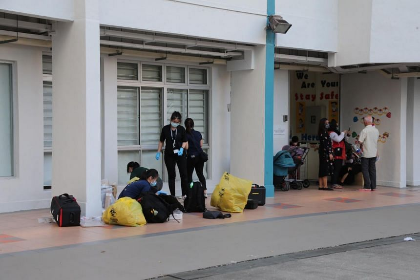 Police officers near where a woman was found lying motionless with multiple stab wounds at the void deck of Block 308 Jurong East Street 32.