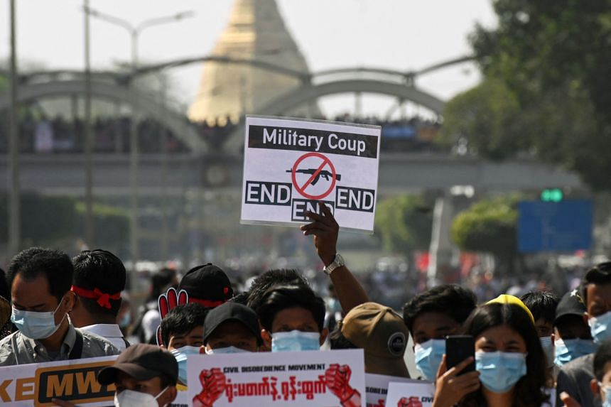 Protesters hold signs as they block a road during a demonstration against the military coup in Yangon, on Feb 17, 2021.