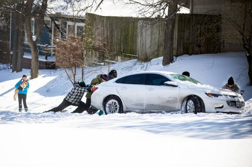 East Austin residents push a car out of the snow on Feb 15, 2021, in Austin, Texas.