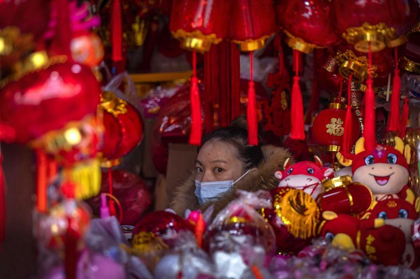 A woman offers lanterns and other Spring Festival decorations for sale in Shanghai, China, on Feb 15 2021.