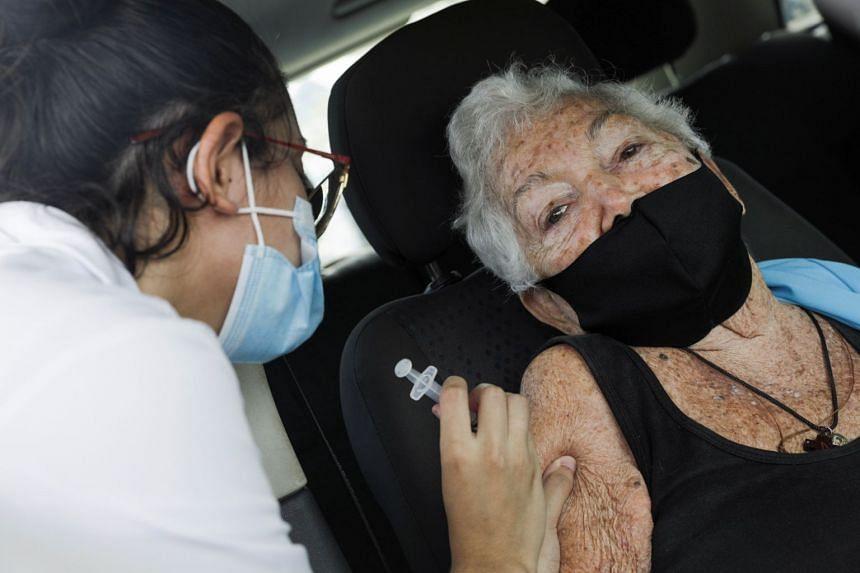 An elderly resident receives a vaccine shot in Rio de Janeiro, Feb 13, 2021.