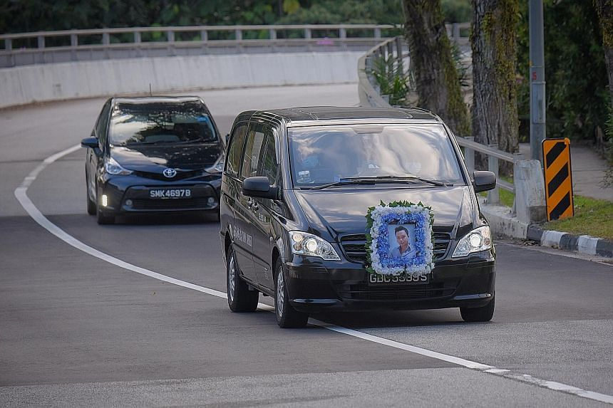 The hearse (above) of Mr Wilson Teo, one of the passengers who died in the Tanjong Pagar crash, arriving at Mandai Crematorium yesterday, where he was cremated following the service, at about 6.30pm. Earlier yesterday, a monk (below) was seen conduct