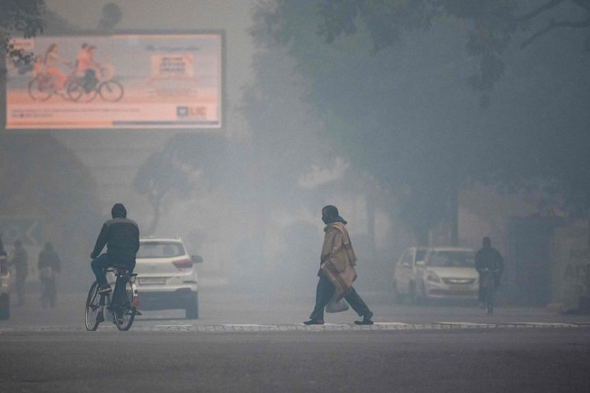 A man crosses a street amid heavy smog conditions in New Delhi, on Jan 15, 2021.