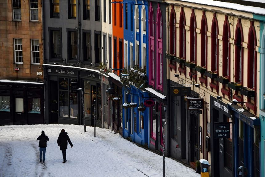 People walk in the snow along a deserted Victoria Street in Edinburgh, Scotland, on Feb 10, 2021.
