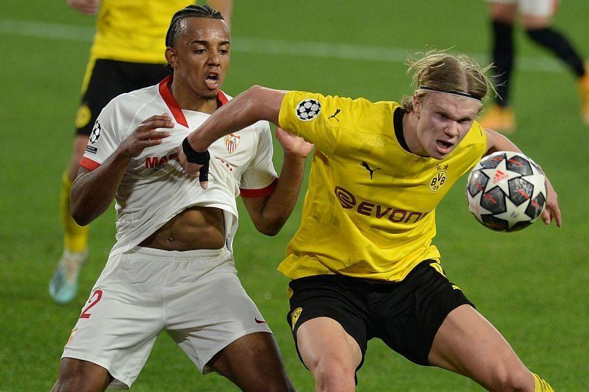 Dortmund's Erling Braut Haaland (roght) challenges Sevilla's Jules Kounde.