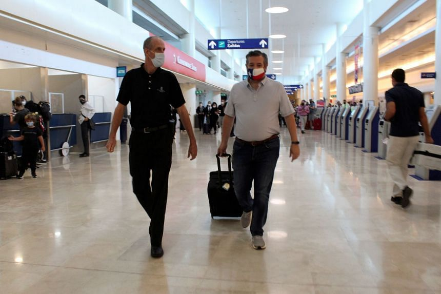 Ted Cruz (centre) walks with an unidentified person at Cancun International Airport before boarding his plane back to the US.