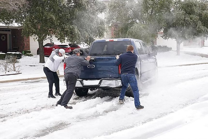 Residents helping a pickup driver to get out of ice on the road in Round Rock, Texas, on Wednesday after a winter storm. The freak cold spell has killed at least 21 Americans in the state and shut down power for days. PHOTO: AGENCE FRANCE-PRESSE