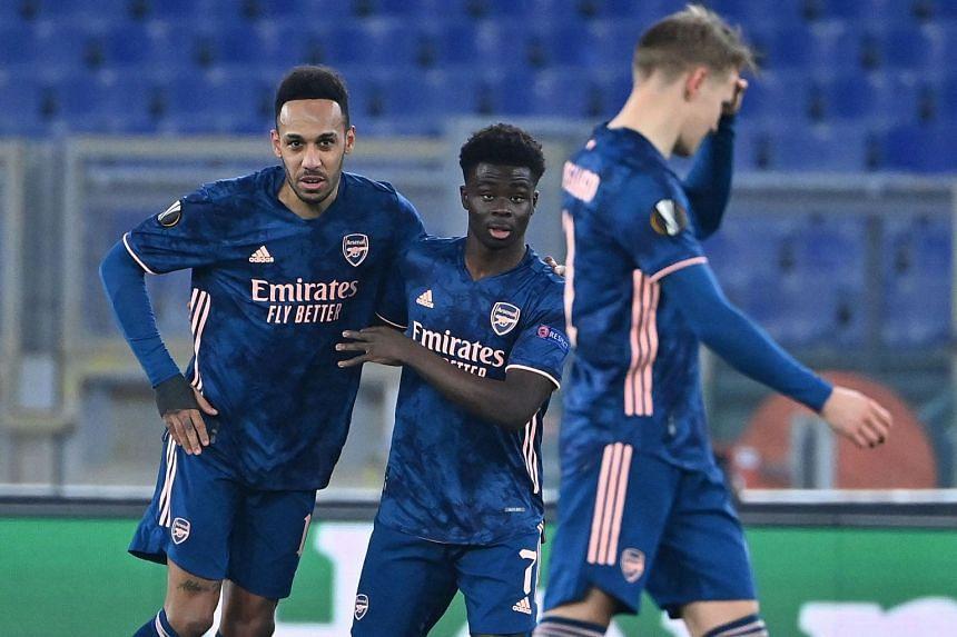 Arsenal's Bukayo Saka (centre) celebrates with Pierre-Emerick Aubameyang after scoring.