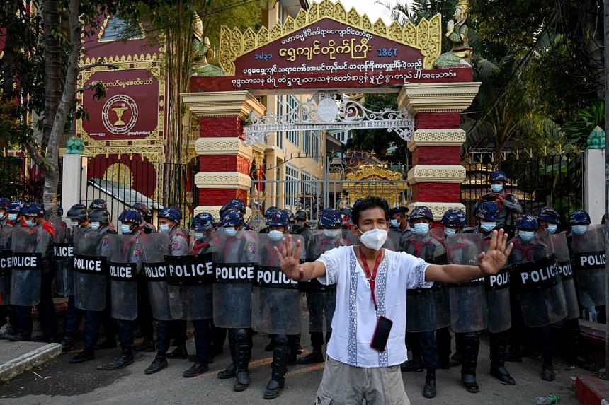 A man gestures towards residents (unseen) as police stand guard at the entrance to a Buddhist monastery where pro-military supporters took shelter after clashes with local residents in Yangon on Feb 18, 2021.