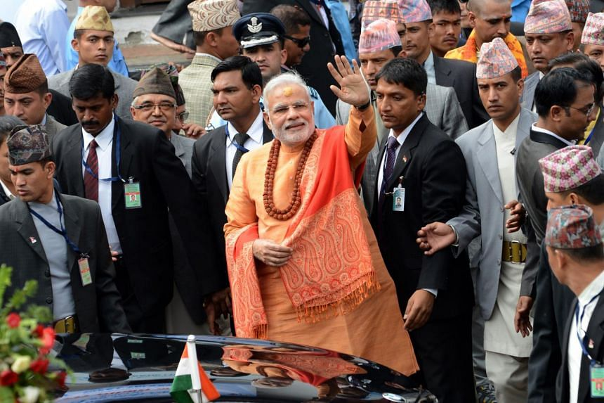 Indian Prime Minister Narendra Modi waves to well-wishers as he leaves following his visit at the Pashupatinath Temple, in Kathmandu, Nepal, on Aug 4, 2014.