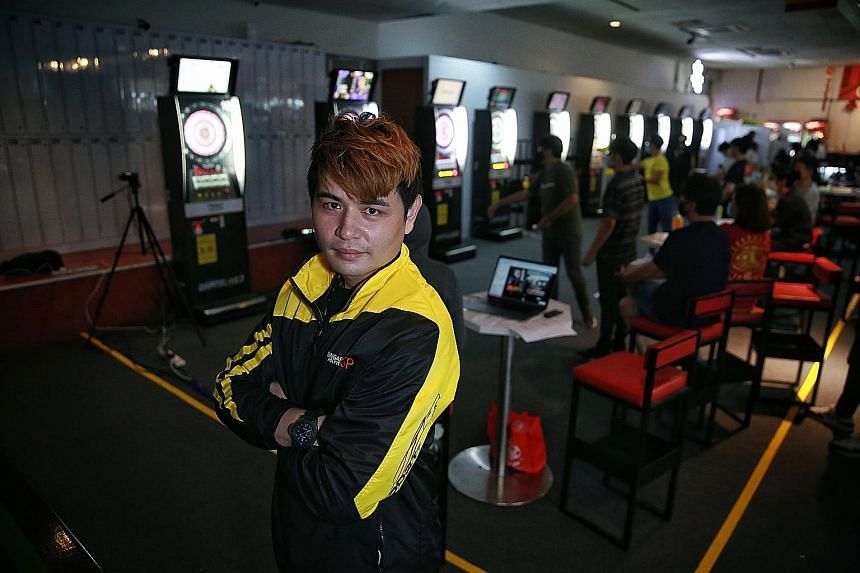 Above: Leslie Lee is a hawker who is also a Dartslive Official Player and a coach at Singapore Polytechnic. Below: The 33-year-old is hoping to one day win Dartslive's The World event as well as nurture the next generation of local players.