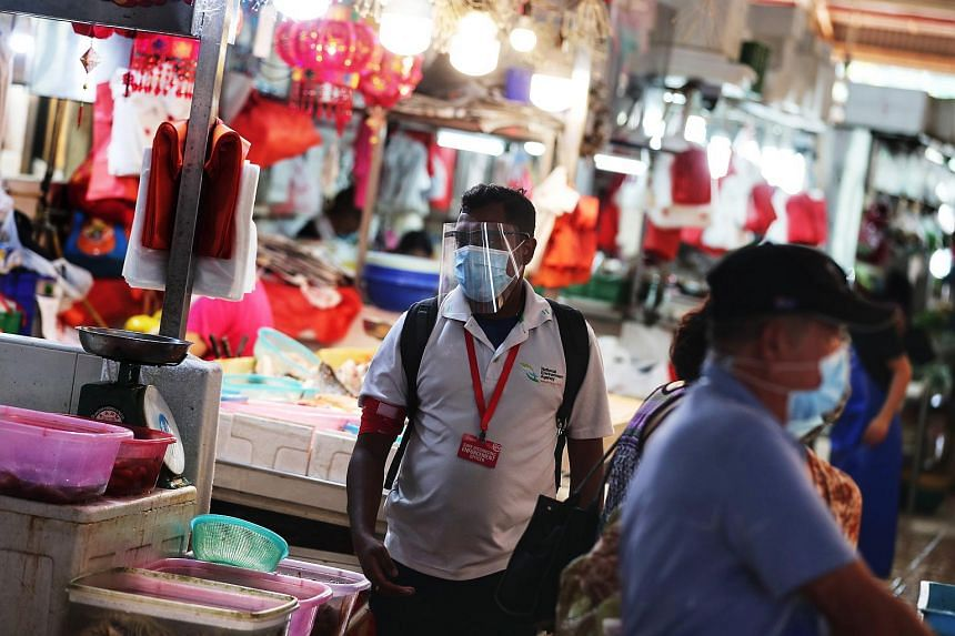 A safe distancing enforcement officer at Ghim Moh Road Market and Food Centre in May 2020.