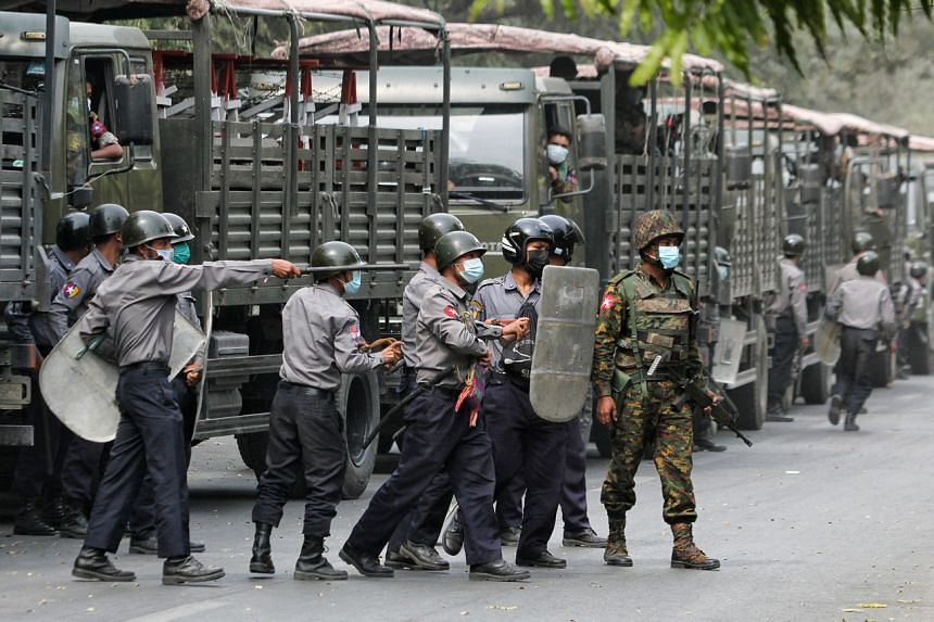 Police and soldiers are seen during a protest against the military coup in Mandalay on Feb 20, 2021.
