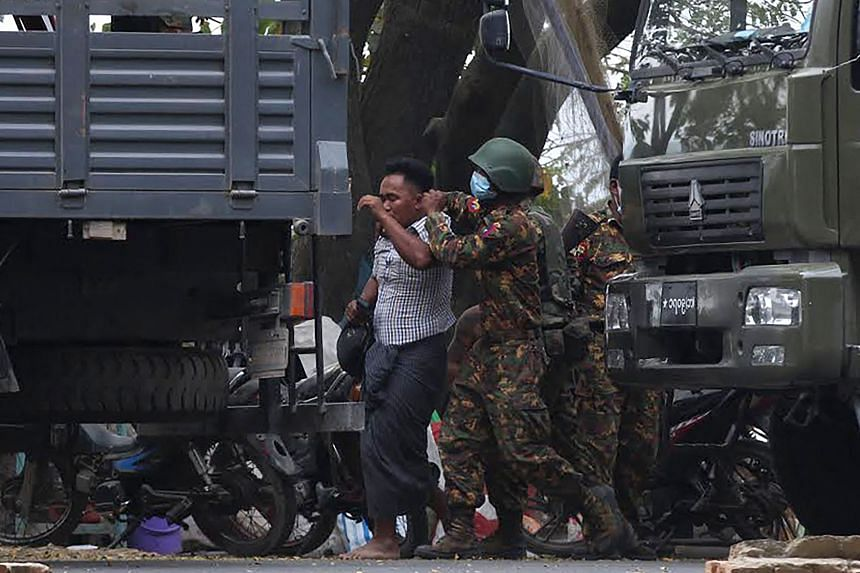 A protester is led away after being detained by security forces during a demonstration against the military coup in Mandalay on Feb 20, 2021.