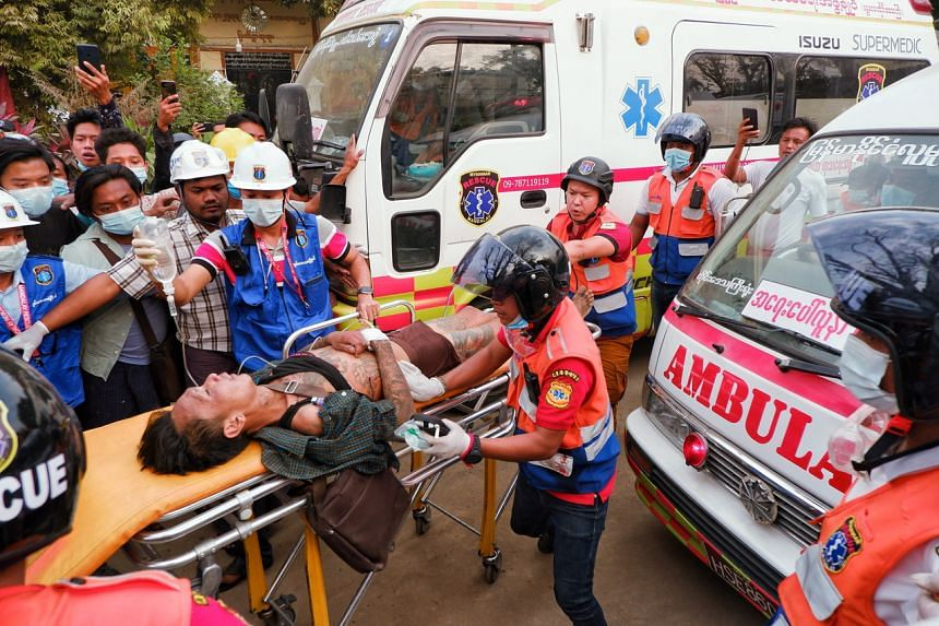 An injured man is carried by rescue workers after protests against the military coup, in Mandalay on Feb 20, 2021.