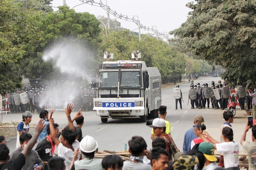 Police officers stand in front of people protesting against the military coup in Mandalay on Feb 20, 2021.