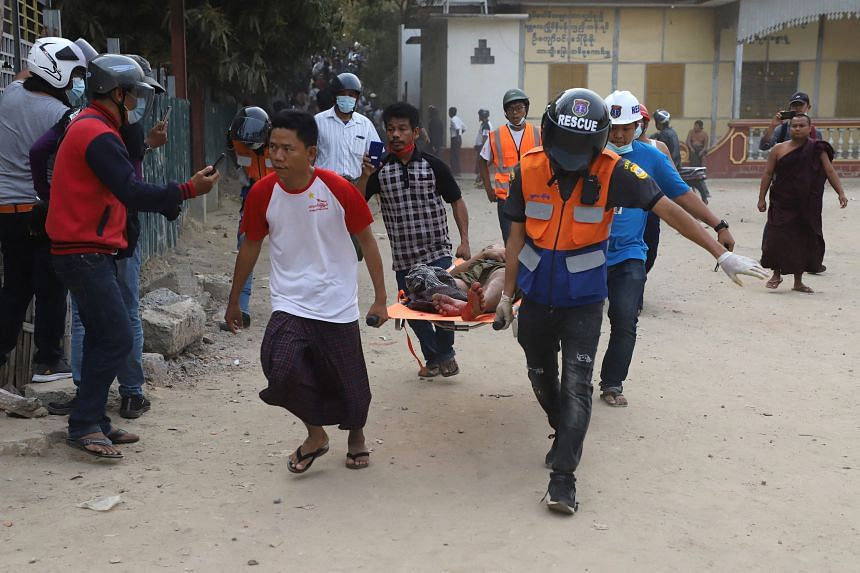 A wounded man is carried on a stretcher by a medical team after security forces opened fire on protesters during a demonstration in Mandalay on Feb 20, 2021.