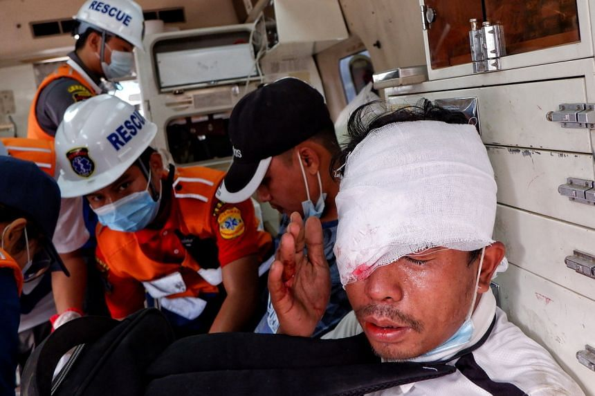 An injured man sits in an ambulance after police fired rubber bullets during a protest against the military coup in Mandalay on Feb 20, 2021.