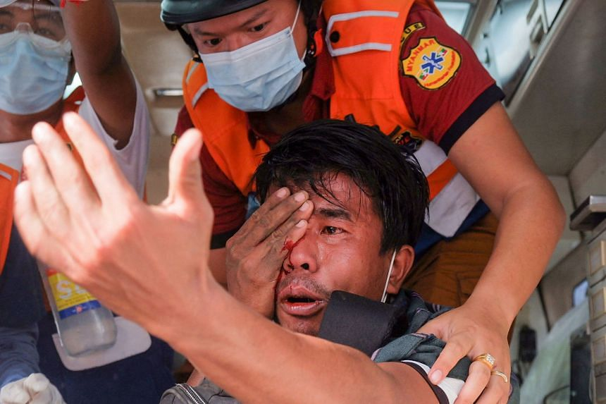 A man injured after being hit with a slingshot fired by security forces receiving treatment by a medical team in Mandalay on Feb 20, 2021.