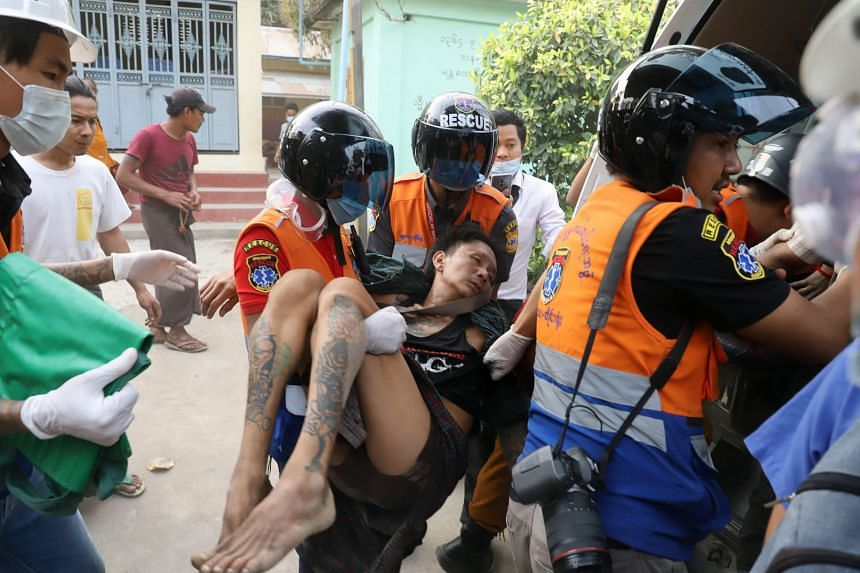 A wounded man is carried by a medical team after security forces opened fire on protesters in Mandalay on Feb 20, 2021.