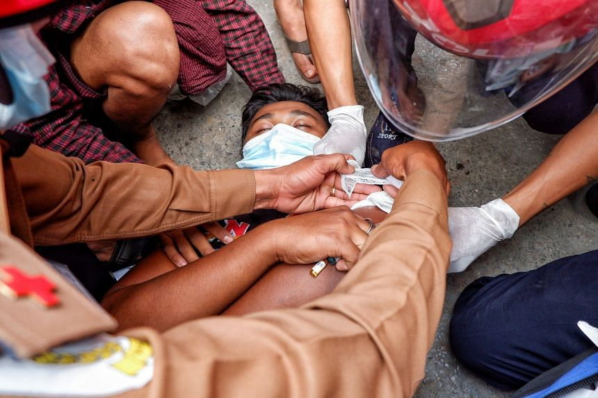 A injured man lies on the ground after the police fired rubber bullets during protests in Mandalay on Feb 20, 2021.
