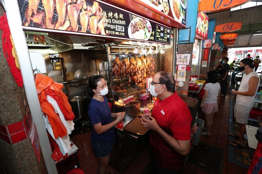 Minister for Communications and Information and MP for West Coast GRC, Mr S. Iswaran, greeting a hawker at Ayer Rajah Food Centre.