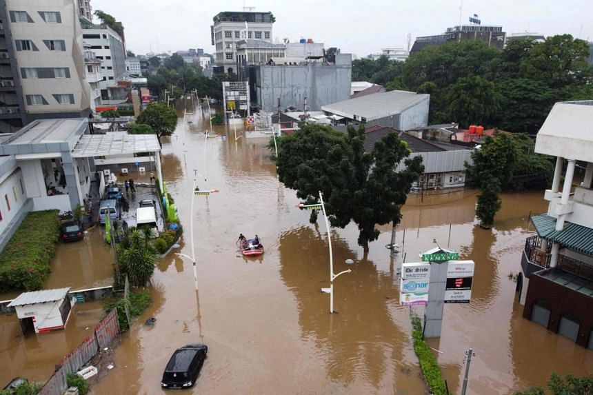 This aerial picture shows people rowing a raft over a flooded road in Jakarta, on Feb 20, 2021.
