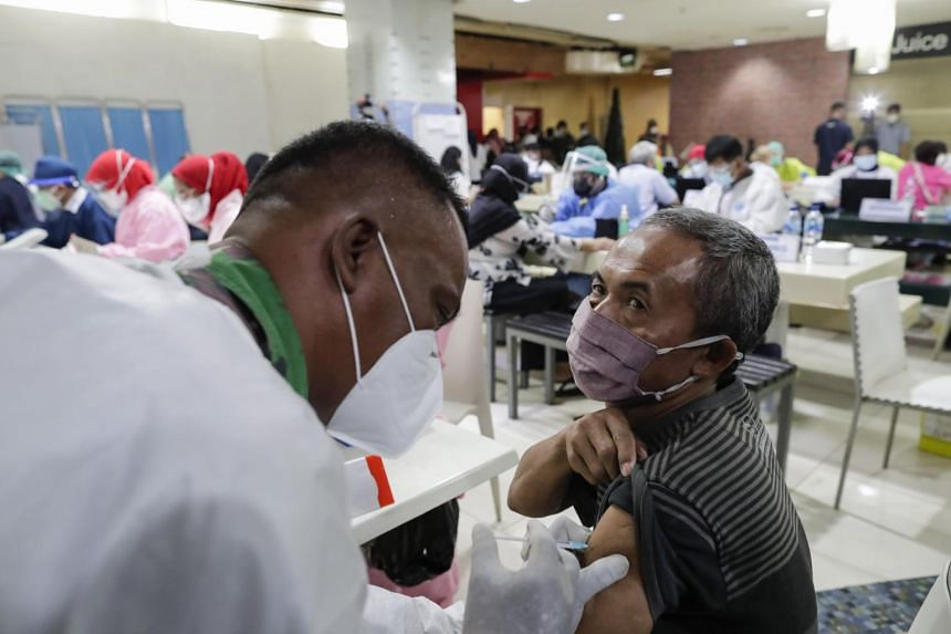 A healthcare worker injects a dose of Covid-19 vaccine on an elderly man in Jakarta, Indonesia, on Feb 17, 2021.