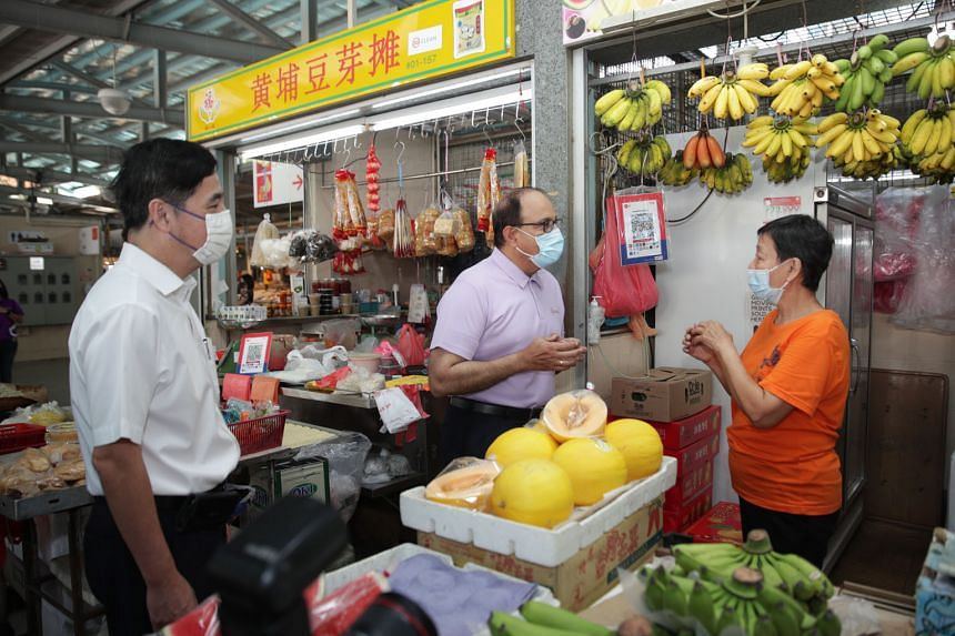Madam Lim Meng Kee, a stallholder at Whampoa Drive Food Centre and Market, with Minister for Communications and Information S. Iswaran and Jalan Besar GRC MP Heng Chee How, who is also Senior Minister of State for Defence, yesterday. Madam Lim, who r
