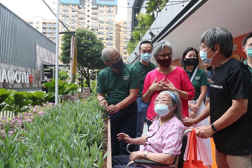 Above: Minister for Social and Family Development Masagos Zulkifli (left) exploring Our Therapeutic Garden with grassroots leaders and residents yesterday. Right: The linear garden at Our Tampines Hub is part of efforts to transform the Tampines esta