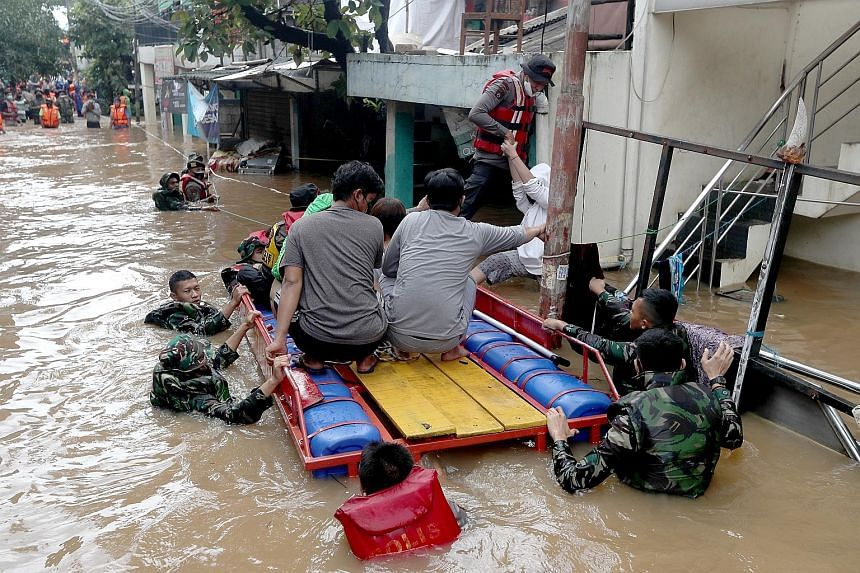 Indonesian military and police officers helping flood victims get into a boat while rescuing residents in Jakarta yesterday.