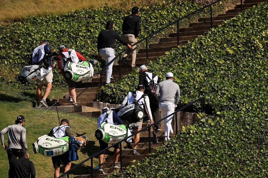 Golfers, caddies and staff return to the clubhouse after play was suspended due to high winds during the third round.
