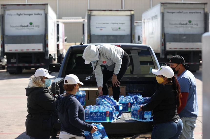 Volunteers load cases of water and emergency food boxes into a truck at the Houston Food Bank on Feb 20, 2021, in Houston, Texas.