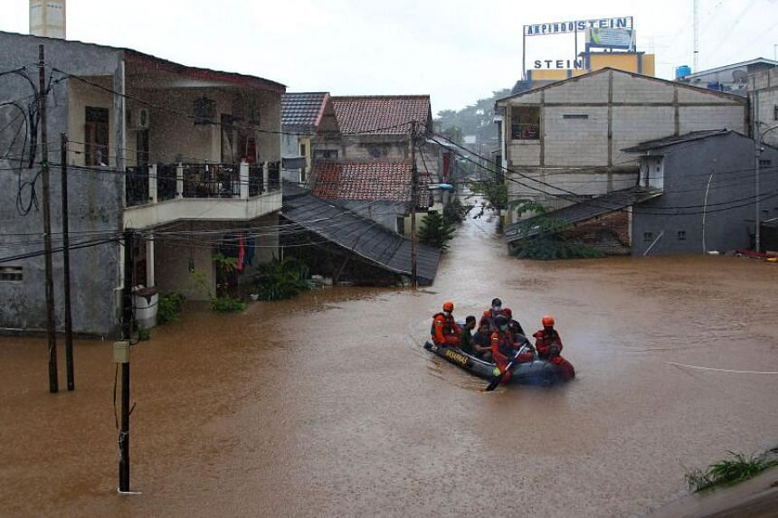 Rescue personnel padding through a flood-affected neighbourhood in Jakarta on Feb 20, 2021.