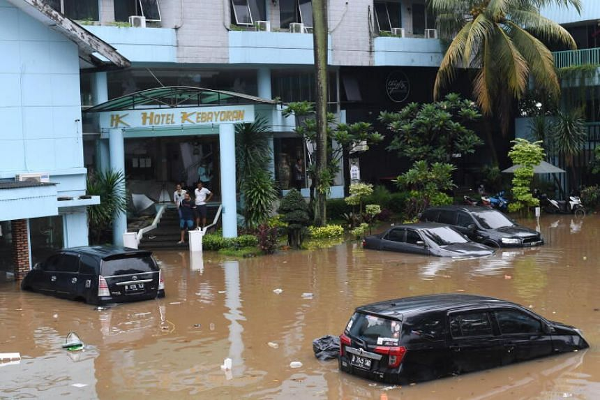 Half-submerged cars are seen outside a hotel in Jakarta, on Feb 20, 2021.