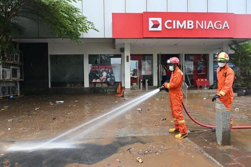 Firefighters hosing away mud and debris following flooding in Jakarta, on Feb 21, 2021.