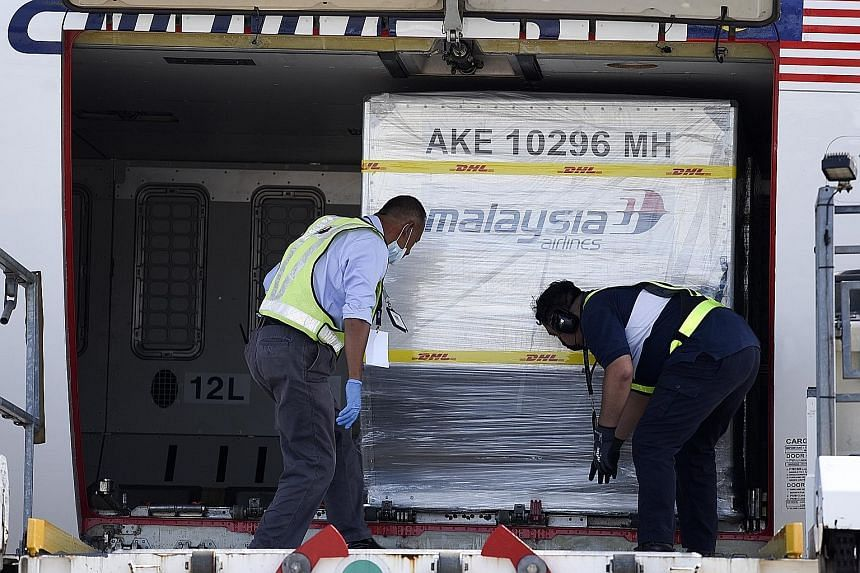 Containers carrying Pfizer-BioNTech Covid-19 vaccines being unloaded from a Malaysia Airlines plane at Kuala Lumpur International Airport yesterday, in a handout photo made available by Malaysia's Department of Information. Malaysian Prime Minister M
