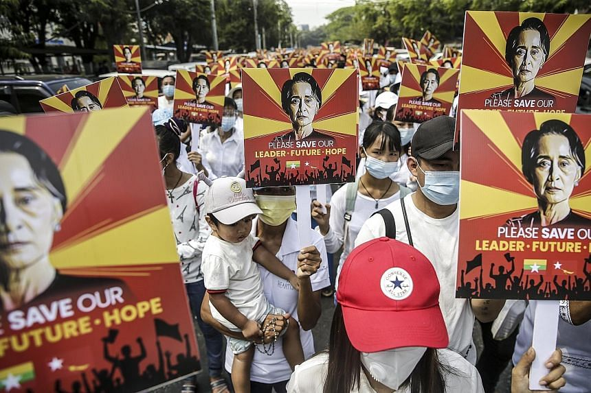 Supporters of elected leader Aung San Suu Kyi holding placards during a rally against the coup in Yangon yesterday. The army seized power after alleging fraud in the Nov 8 election, detaining Ms Suu Kyi and others. PHOTO: EPA-EFE