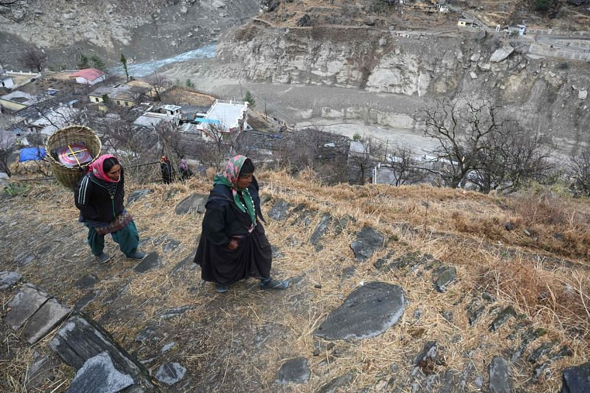 Women from Raini Chak Lata village walk along a mountain path in Chamoli district, on Feb 10, 2021.