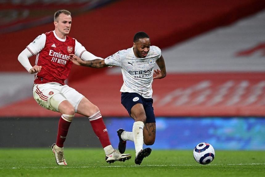 Arsenal's Rob Holding (left) vies with Manchester City's Raheem Sterling during the match at the Emirates Stadium in London on Feb 21, 2021.