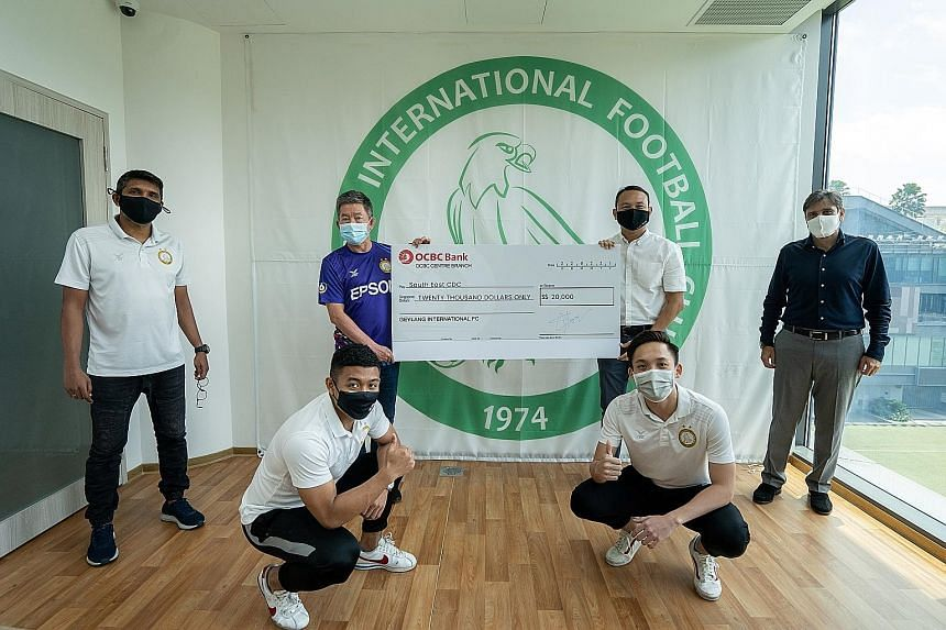 Geylang International committee member Carlo Nohra (far right) watches on while South East District Mayor Fahmi Aliman receives a cheque for $20,000 from Geylang chairman Thomas Gay (in blue) yesterday. The money will benefit the district's underpriv