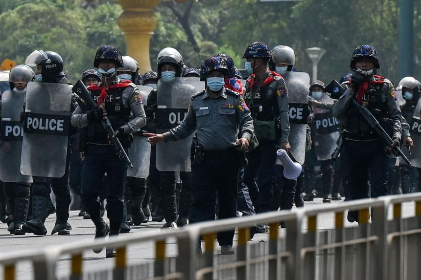 Police advance towards protesters demonstrating against the military coup in Yangon, on Feb 22, 2021.